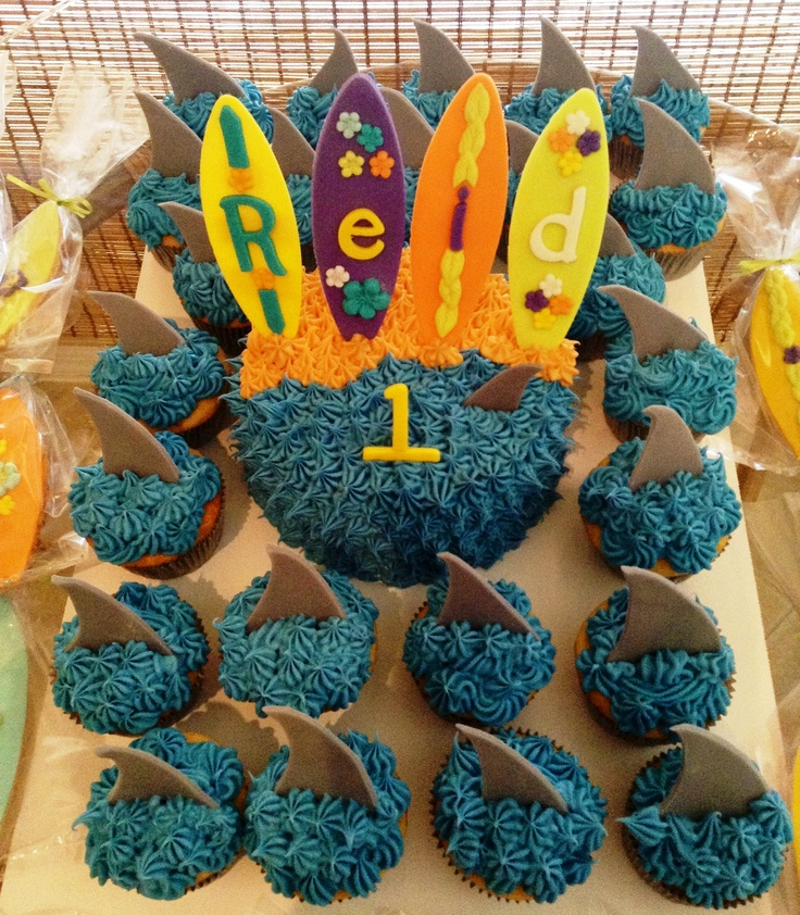 Surfboard smash cake and shark fin cupcakes