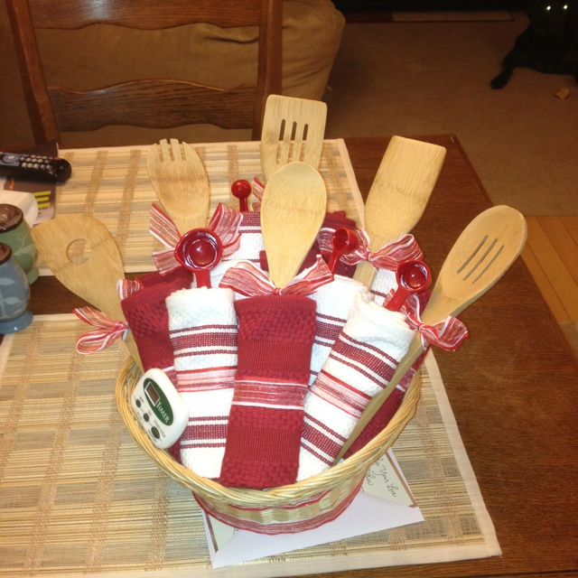 Wedding gift! All you need is a basket, a set of wooden spoons 4 or 5, measuring spoons (I used same color as towels for effect), hot glue gun, ribbon, 5 small dish washing towels, and 6 regular kitchen towels. Just roll the towels up with a piece of card board at the start end for stability. Then hot glue ribbon around towel to hold its shape the glue may go through the ribbon so put a piece of paper between towel and ribbon after ribbon is glued pry the paper away.
