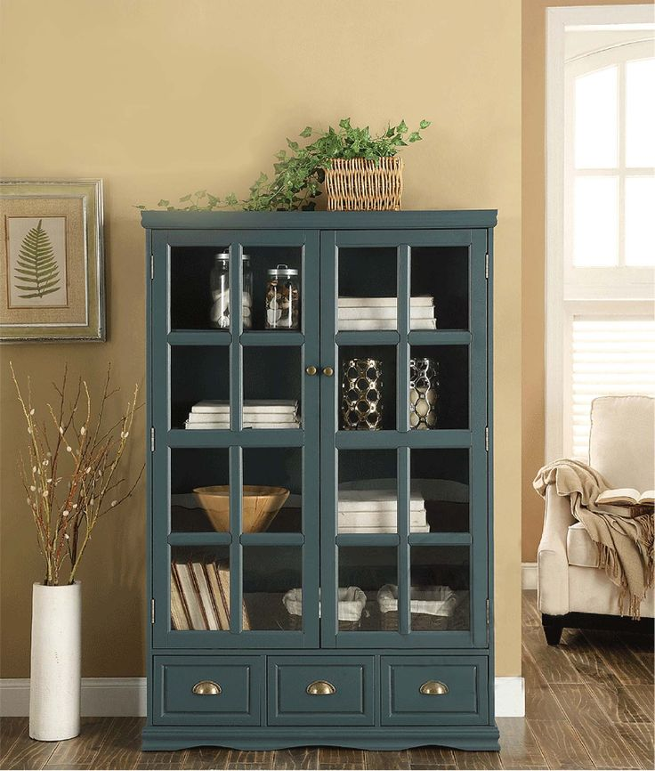 Темно-серый книжный шкаф с прозрачными дверцами и выдвижными ящиками в интерьере комнаты купить https://lafred.ru/catalog/catalog/detail/45307446236/