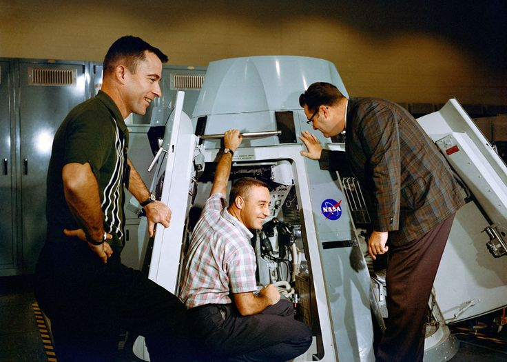 Astronauts Virgil I. Grissom (center) and John W. Young (left), prime crew for the Gemini-Titan 3 mission, are shown inspecting the inside of Gemini spacecraft at the Mission Control Center at Cape Kennedy, Florida, on November 9, 1964. (NASA)