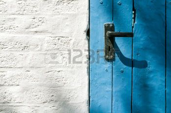 Weiß gestrichene Backsteinwand mit alter blauer Holztür mit Türgriff - Lizenzfreie Bilder