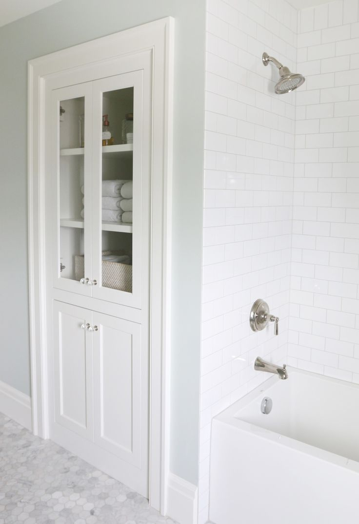 built-in linen closet, marble, subway tile with gray grout. As the wall**** clear glass through