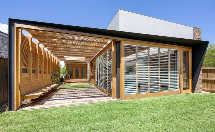 This smart extension to a suburban home includes kitchen, living and dining spaces that are enclosed on adjacent sides with louvred, sliding walls