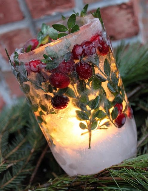 Pretty ice candle holder made with cranberries and green plant sprigs.
