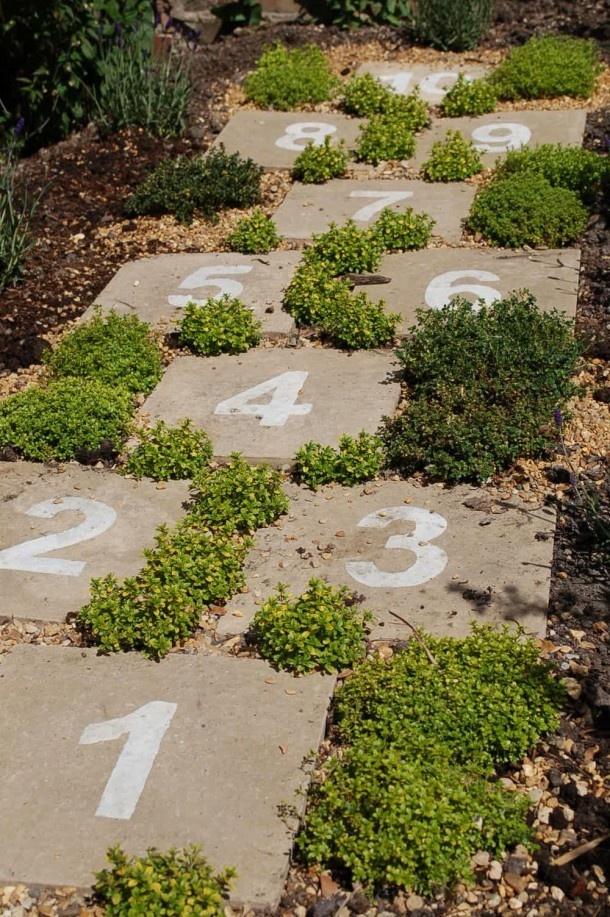 Hinkelpad van oude (stoep)tegels, genummerd met betonverf en met vetplantjes ertussen. Door Tiara