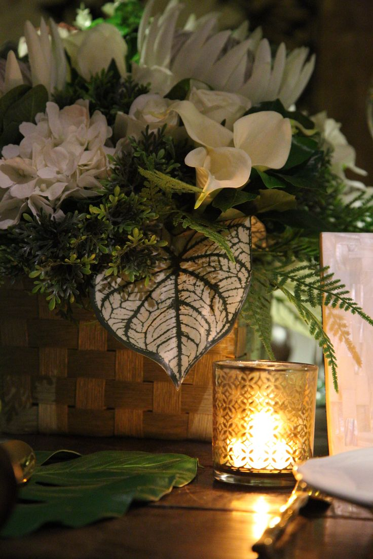 Gold plumeria votive candle holder with white tropical flowers.  White and gold polynesian wedding