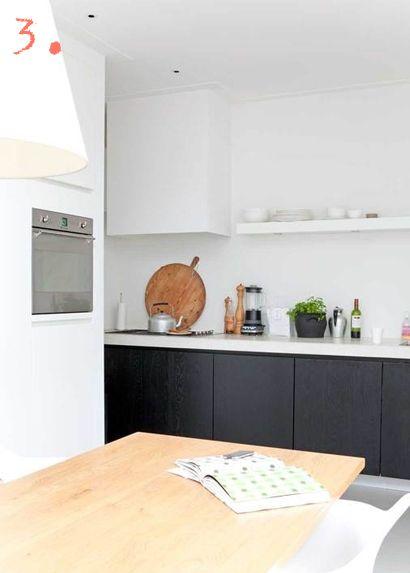 Zwarte keuken met wit blad, mee-gestucte schouw.