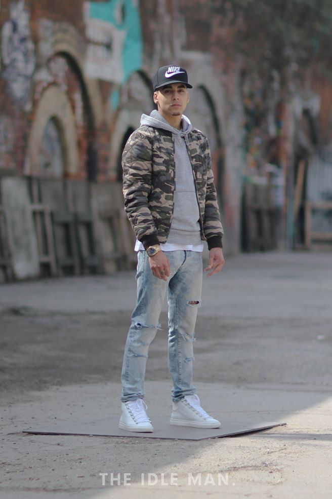 Men's street style, go for an army green camo bomber jacket, wear it with a grey hoodie, a snapback and white shoes for a street look.   Shop men's clothing, accessories and shoes at The Idle Man