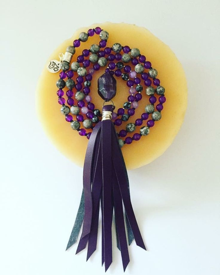 """This unique, hand-knotted Mala has a beautiful chevron Amethyst guru stone and a handmade vegan leather tassel! It's comprised of 108 beads (6 and 8mm), including Snowflake Obsidian, Amethyst, Alexandrite and White Picture Jasper. Hangs at about 24"""" to the end of the tassel."""