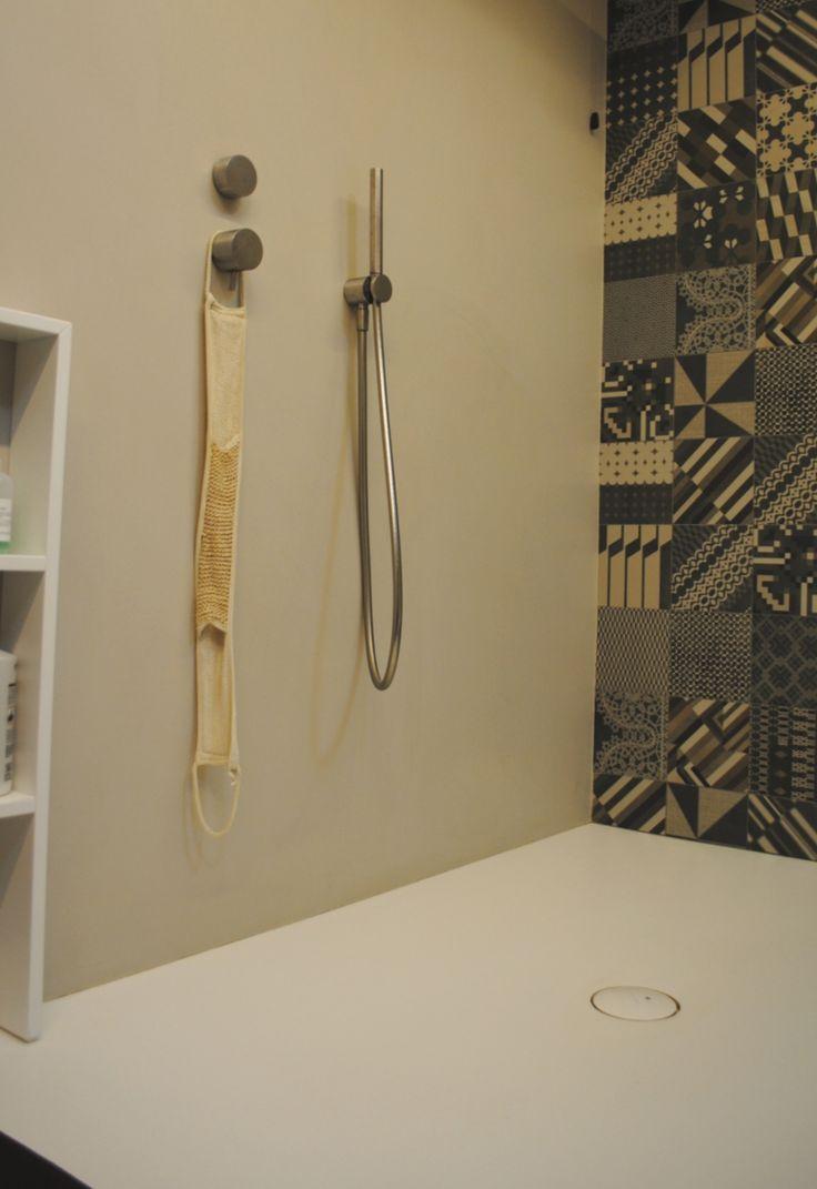 Piatto doccia in resina bianca in continuità con pavimento in resina grigio.