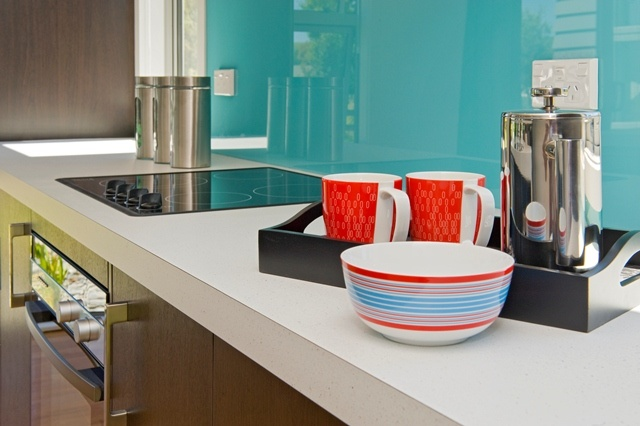 Colourful splashback and stainless steel for the kitchen.