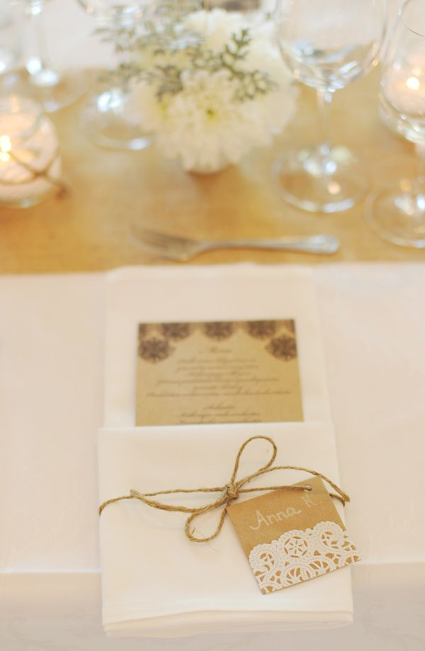 Menu card in a pocket folded napkin tied together with package string and a handwritten place card is gorgeous