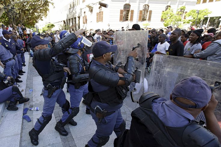 Police in riot gear clash with students outside the Parliament building in Cape Town