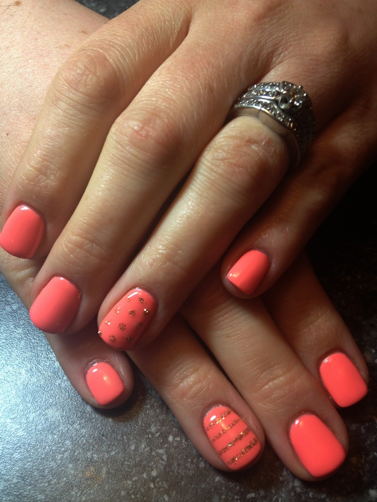 Coral gel nails with small glitter accents
