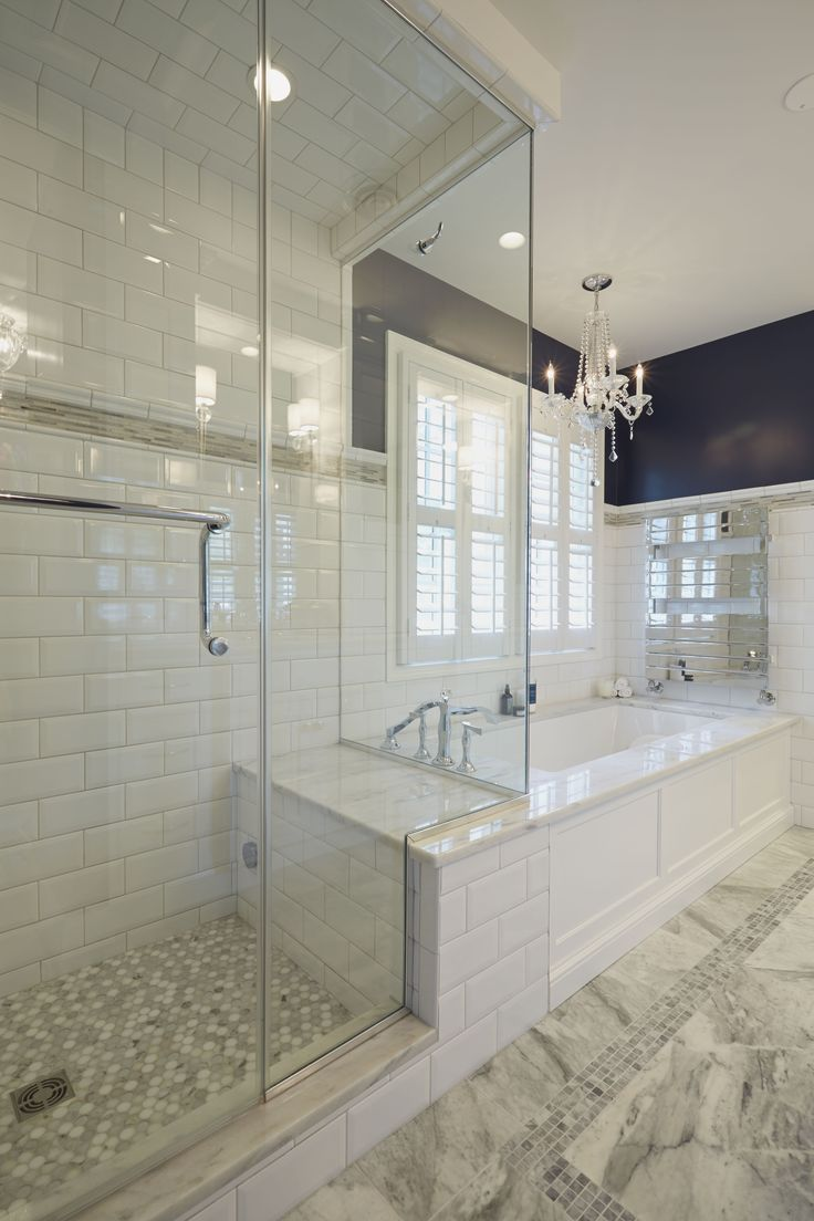 Glass enclosed shower with bench connected to the platform of a soaking tub with heated towel racks above.