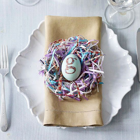 How to create this pretty paper-strip-nest place setting. To create the nest, shred (paper shredder works best) decorative or scrapbook paper, or recycle gift wrapping paper or magazines or even newspaper and form into a ball large enough to accommodate a dyed Easter egg. Add monograms or names to the eggs and they can serve as place cards.