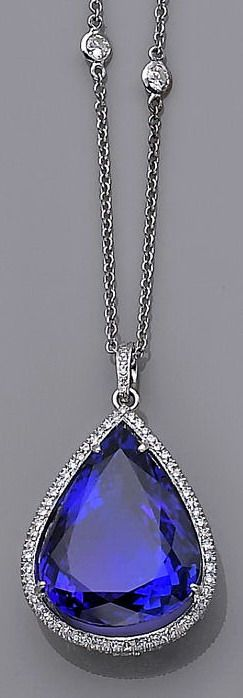 A tanzanite and diamond pendant-necklace centering a pear-shaped tanzanite with a round brilliant-cut diamond surround and gallery, completed by a collet-set round brilliant-cut diamond-set chain; tanzanite weighing approximately: 37.35 carats; estimated total diamond weight: 2.55 carats; mounted in eighteen karat white gold; length: 16¼in.