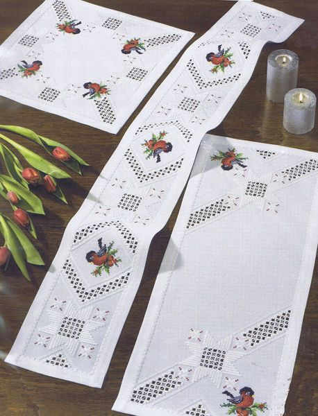 Crisp white table mats with openwork areas and little robins of pine sprigs.