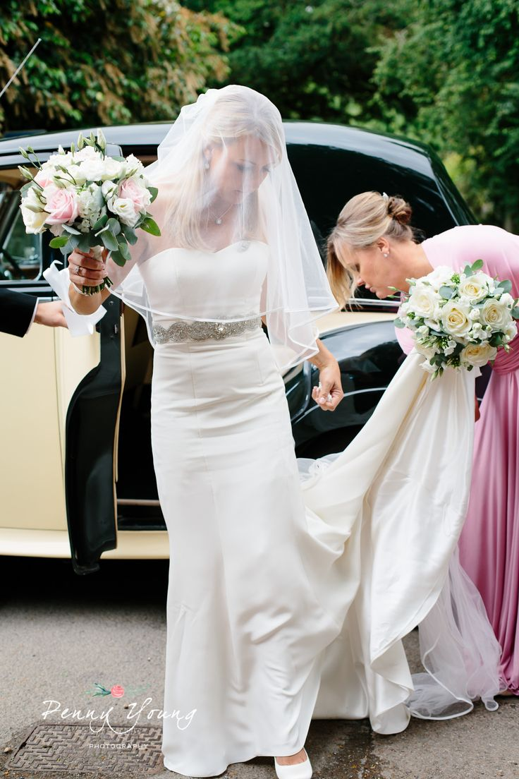 Bride arriving at the church. Summer wedding in Kemble Church followed by a country garden reception nearby. Photography by Penny Young Photography.