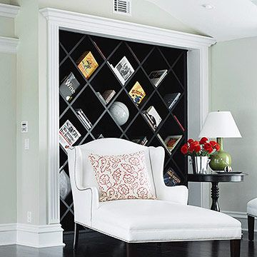 Diamond-shape cubbies instead of flat shelves in this wall unit decoratively store books and magazines diagonally. Angled organization holds rolled-up throws and other round memorabilia without letting it roll away.