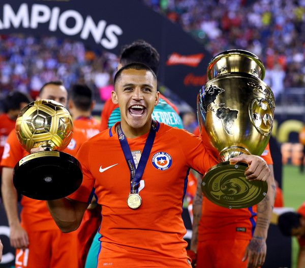 Alexis Sánchez with the Golden Ball and Copa America trophies.