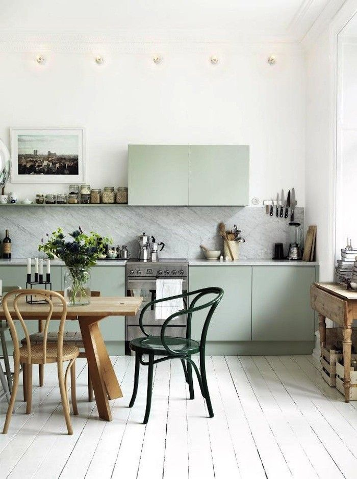 I like the subtle mix of tones here: pale floors, soft green/blue cabinets, gray marble, white walls
