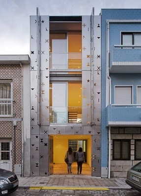 House in Póvoa de Varzim, Portugal hidden by  aluminium shutters perforated with symbols.
