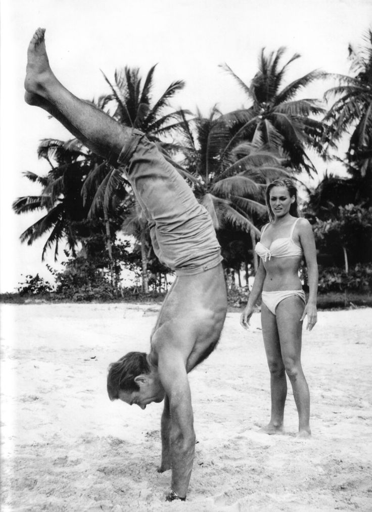 "Sean Connery teaching his co-star, Ursula Andress, how to do a handstand on the set of the first James Bond movie, ""Dr. No"" (1962)"