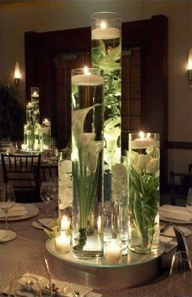 Tall, clear vases filled with water, flowers and a floating candle on top. Set on a mirror lazy susan. Maybe exchange flowers for colorful fruit for a less expensive option.