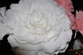 white paper flower - there's a lot of be said for huge white crepe paper flowers if they are made well.  And to waterproof them, simply spray 2-3 coats,  very lightly each time, with clear Varathane type spray.    They'd be really lovely used both for wedding ceremony and reception venue decor.  (Image scads of them hanging down from the ceiling at various heights, using invisible fishing line!).