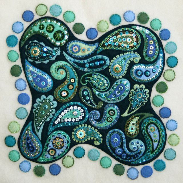 ARTIST a little bit of just because  TITLE Dream Fragments    Each paisley was individually beaded/sequined and then stitched to the blue backing. The blue was then quilted to the cream (bit hard to see in these photos, but the quilting makes each of the paisleys pop up from the background). The circles around the outside were then stitched directly onto the background and then beaded. The entire piece is backed with felt and 'signed' in stitching on the back.