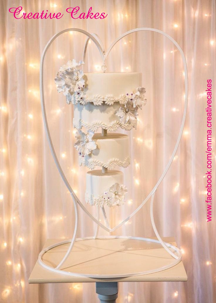 'The Chandelier Cake'  This design offers you something a bit different and unique for your wedding cake. Using simple wired flowers with pearl and diamante centres, small filler flowers with purple centres in a elegant modern white finish.