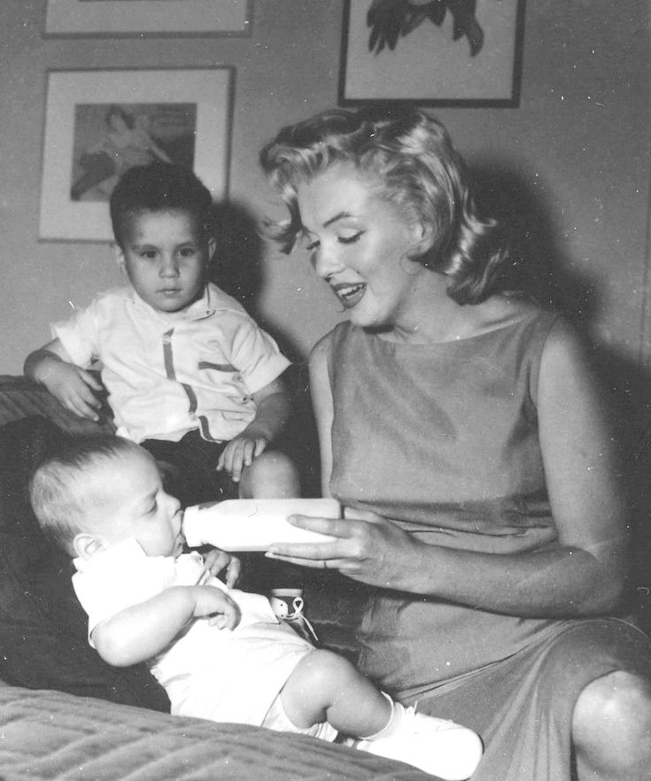 Marilyn with William Metzler and a baby for the Milk Fund, 1957.