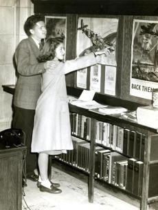 """Oct. 29, 1942: Paul Lambert of Dorchester and Emily Scott of Hyde Park visited the War Information Center at the Boston Public Library. The Works Projects Administration, or WPA, provided assistance for every library to become a War Information Center, """"making available all the latest facts, reports, directories, regulations and instructions for public use."""" Boston Globe Archives 
