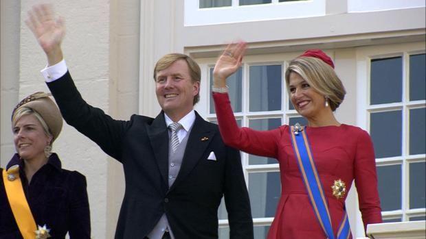 Koning Willem-Alexander, koningin Máxima en prinses Laurentien wuiven vanaf het balkon van Paleis Noordeinde naar de massaal toegestroomde belangstellenden.