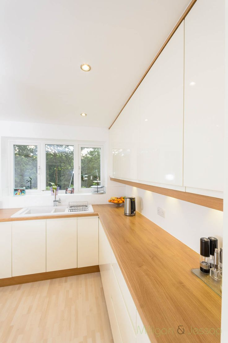 The clients chose high gloss handleless Remo doors in Alabaster from Second Nature by Milligan & jessop this gives alot of light into the room. The worktop is an Oak style Laminate which complements the European Oak surrounds and brings the whole kitchen together.Plinths and cornice in European Oak add a touch of warmth to the otherwise bright kitchen. A peninsula breaks up both parts of the room, adds workspace and allows for cooking whilst facing guests or family.