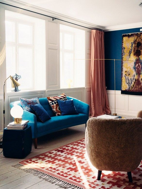 Retro living room with blue sofa, patterned rug, orange curtains, oversized art, and navy walls