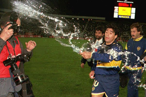 Diego Armando Maradona le tira agua a los fotógrafos en el Monumental por la Supercopa 1997