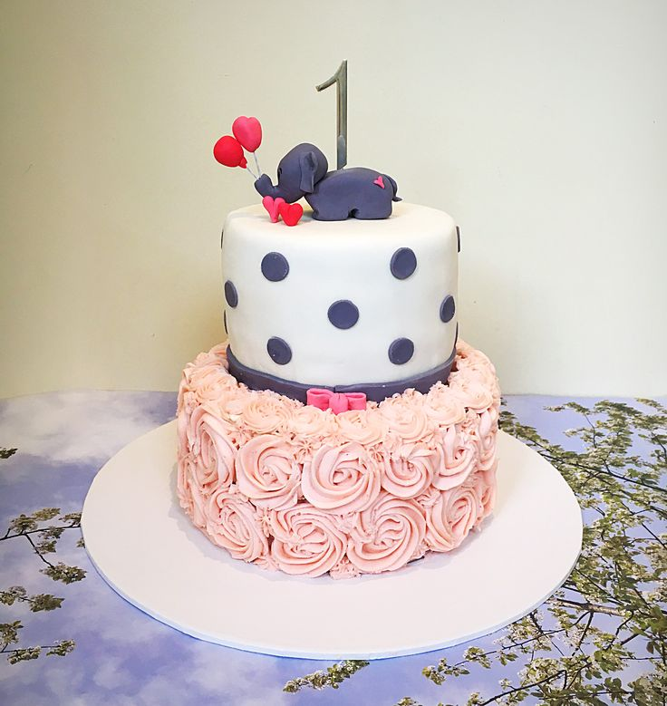 Cute first birthday cake with hand crafted baby elephant, matching grey polka dots and pink buttercream roses
