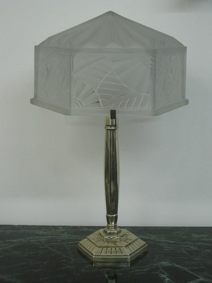 """Degue Table Lamp - A French Art Deco Table Lamp signed by the French artist """" DEGUE """" in clear frosted molded Glass Shade enhanced by intricate leaves and geometric motif with polished details. Stem with multi-tier hexagonal base embellished with Art Deco ornamental design in Silvered Bronze base. Re-plating available upon request.  Reference #: TL8704  Measurement: Height: 20 in. (50.8 cm) Diameter: 12.5 in. (31.75 cm) Shade Height: 7 in. (17.8 cm) Diameter: 12.5 in. (31.75 cm)"""