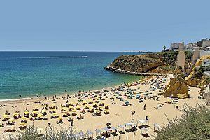 Guia de Praias do Algarve | Popular Villas - A praia do Túnel é a primeira praia a leste da marina de Albufeira e encontra-se situada no meio de uma área urbana, perto da cidade velha de Albufeira. O acesso à praia faz-se através de um túnel escavado na falésia de calcário, situada entre as ruas estreitas da vibrante cidade velha de Albufeira, onde irá encontrar muitos bares, restaurantes convidativos e lojas de artesanato. Coordenadas de localização: GPS N 37° 5' 11.68'', W -8° 15' 10.39''
