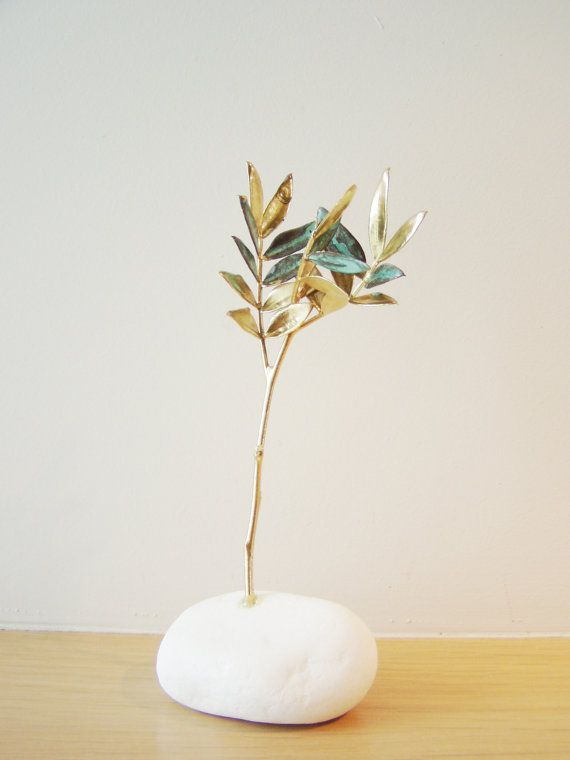 Schinus tree sculpture is a real schinus twig, electroplated with gold and copper.  A gold and copper patina schinus twig on white stone.    It looks