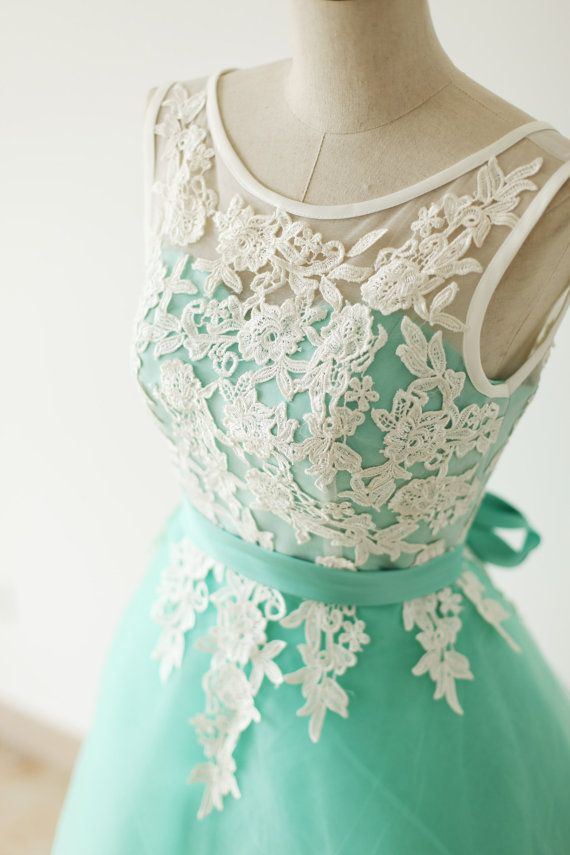 Lovely color combo of ivory and aqua blue. Modest front neckline with deep V back. Extra lace appliques on the skirt and then faded to plain.