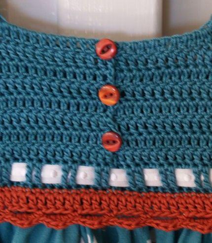 Un partido sorprendentemente bonito vintage margaritas sobre fondo verde azulado acompañados de lunares de hoy en día.  La blusa es a mano de ganchillo en hilo 100% algodón teal con ribete ondulado alrededor de las sisas y parte inferior de la blusa en rust. La falda del vestido es 100% algodón vintage pre-lavado con un anillado/dobladillo en moderno lunares en tonos de verde azulado, óxido y verde sobre un fondo blanco. Bonitos tonos de botones de plástico de ojo de gato vintage de teal...