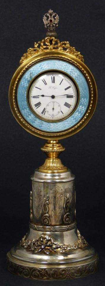 PAVEL BUHRE RUSSIAN SILVER GUILLOCHÉ CLOCK Antique Russian Pavel Buhre pocket watch set in Russian silver and enamel guilloche presentation mounting. Watch has white enamel face with black Roman numerals and notches. Has metallic cobalt blue hour, minute and sub-second hands. Mounting has raised floral ribbon design throughout base. Has gold wash mounting with guilloche border. Holds 1894 assayer's mark with 88 silver purity mark and Moscow town mark.