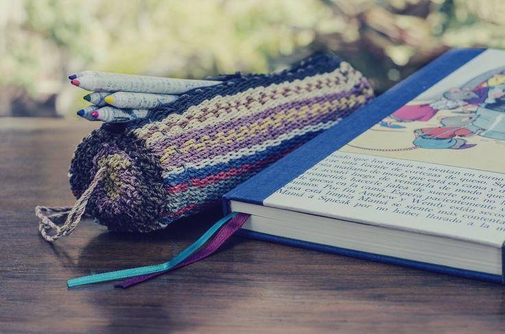 Cuaderno hecho a mano forrado con hojas de libros reutilizados. Cartuchera tejida con fibras de chaguar. Lápices de colores, hechos con papeles de diario reutilizados. (Obra Inspiración Sustentable)