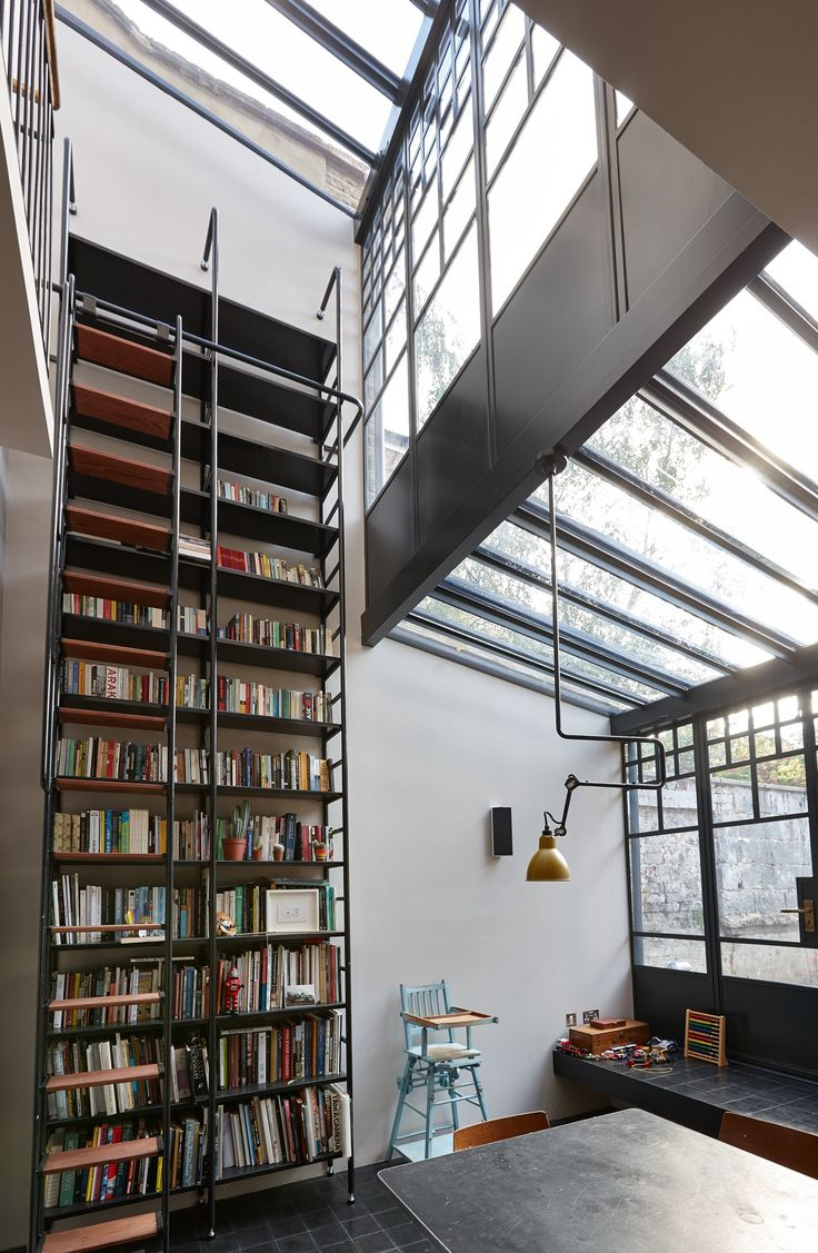 Trombe - An Internal shot of a double height steel frame lean to extension to create a dining room space. The space includes a custom built bookshelf to match. A modern yet industrial style extension.