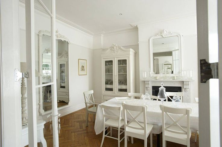Heavenly white dining room with a stunning Rococo mirror