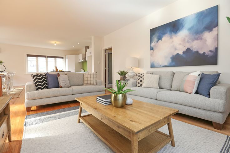 Lounge room, living room, contemporary styling, large sofa, cloud artwork, neutral colour palette, tray side table, woollen floor rug, polished floorboards, cross cushion, indoor plant, open plan kitchen, dining, living