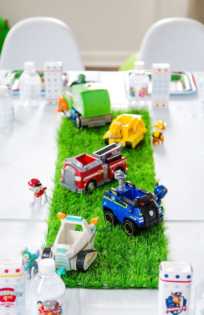 """Adorable party table centerpiece with """"grass"""" and vehicles from a Chic Paw Patrol Birthday Party at Kara's Party Ideas. See all the pawsome details at karaspartyideas.com!"""